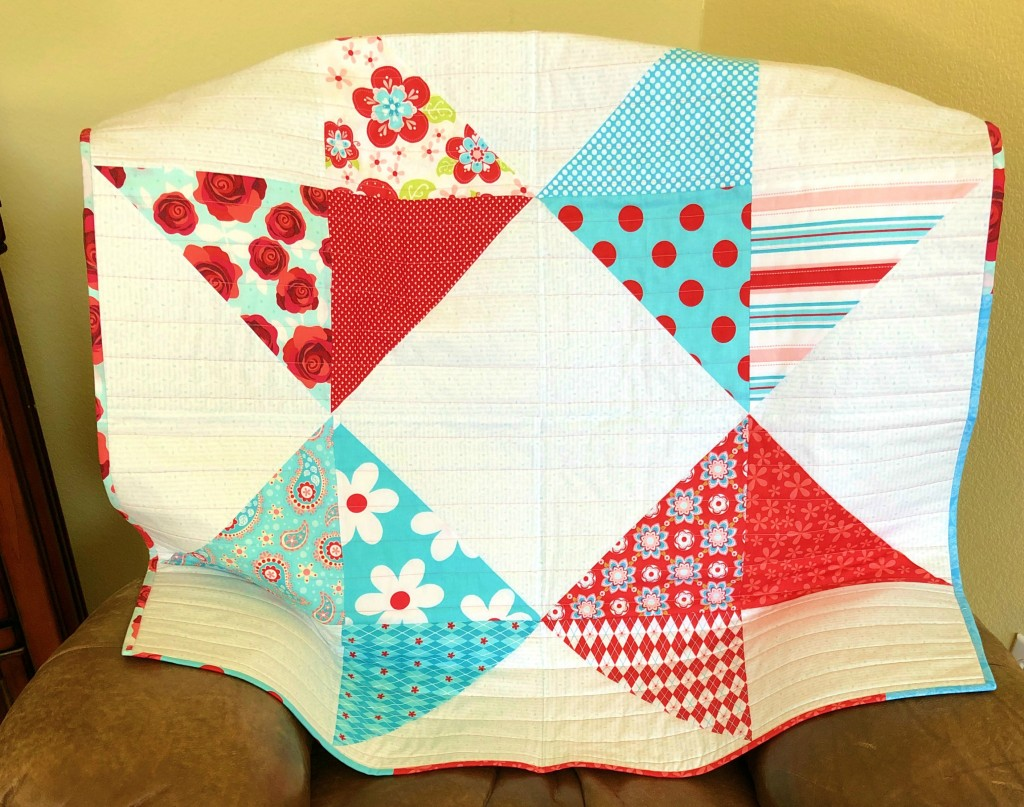 layer cake baby quilt in aqua red